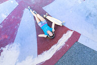 Female longboarder with earphones lying in halfpipe - MAEF12615