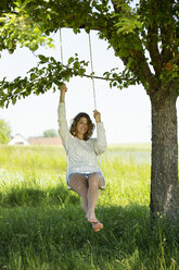 Smiling young woman sitting on swing - MAEF12618