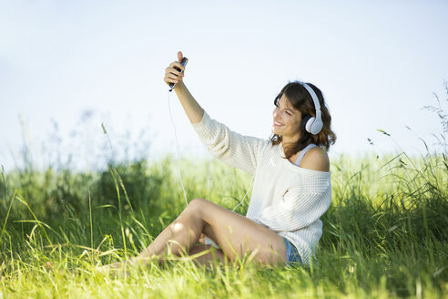 Smiling young woman with earphones taking a selfie - MAEF12627
