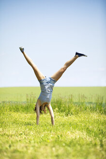 Young woman doing handstand on meadow - MAEF12630