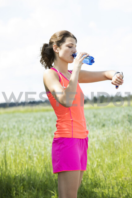 Smiling young woman drinking water and looking on smartwatch - MAEF12642