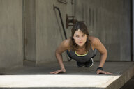 Woman doing push ups outdoor - MAEF12645