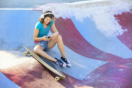 Female longboarder with earphones using smartphone - MAEF12651