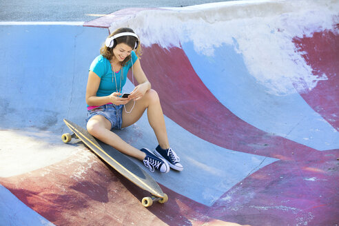 Female longboarder with earphones using smartphone - MAEF12651
