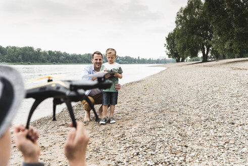 Father with two sons playing with drone at the riverside - UUF13919