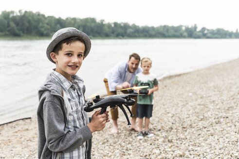 Portrait of smiling boy with father and brother playing with drone at the riverside - UUF13922