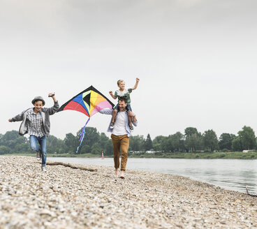 Happy father with two sons flying kite at the riverside - UUF13928