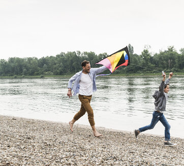Happy father with son flying kite at the riverside - UUF13931