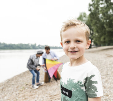 Portrait of smiling boy with father and brother holding kite at the riverside - UUF13934