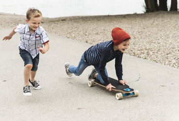Happy boy running next to brother on skateboard - UUF13937