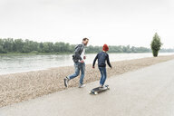 Happy father running next to son on skateboard at the riverside - UUF13940