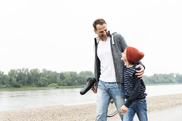 Happy father and son walking with unicycle at the riverside - UUF13943