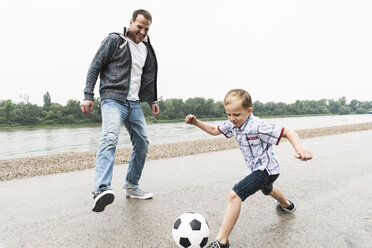 Happy father and son on playing football at the riverside - UUF13946