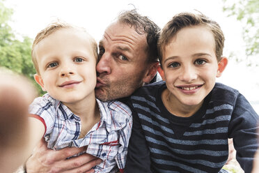 Selfie of happy father with two sons outdoors - UUF13949