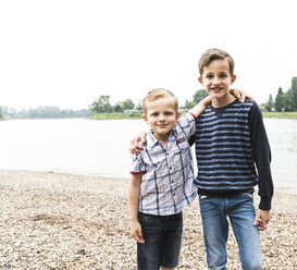 Portrait of two smiling boys embracing at the riverside - UUF13952