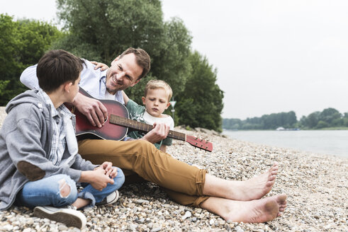 Happy father with two sons sitting at the riverside playing guitar - UUF13955