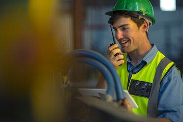Engineer in industrial plant inspecting machines, using walkie-talkie - ZEF15584