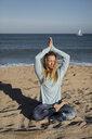Woman doing yoga on the beach, lotus position - MAUF01431
