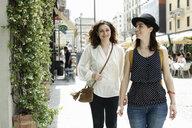 Two women strolling along city street, Milan, Italy - CUF21234