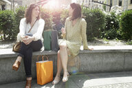 Two women with shopping bags sitting on wall chatting, Milan, Italy - CUF21237