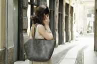 Woman using smartphone on traditional street, Milan, Italy - CUF21240