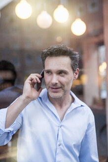 Mature man talking on smartphone in front of shop window - CUF21270