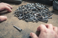 Pair of hands, one screw standing out from pile of different sized screws - CUF21273