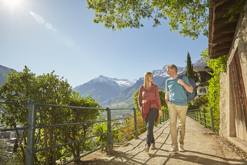 Mature couple hiking along country road, Meran, South Tyrol, Italy - CUF21294