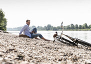 Mature man with bike and smartphone sitting at Rhine riverbank - UUF13979
