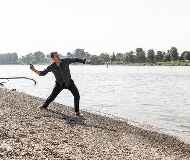 Mature man throwing stone at Rhine riverbank - UUF13991