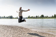 Mature man jumping in the air at Rhine riverbank - UUF13994