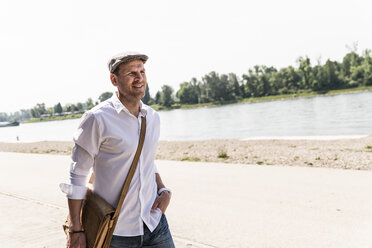 Mature man wearing flat hat at Rhine riverbank - UUF14018