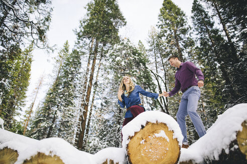 Couple in forest climbing on snow-covered logs - ISF07627