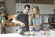 Mid adult couple making cup of tea in kitchen - ISF07765