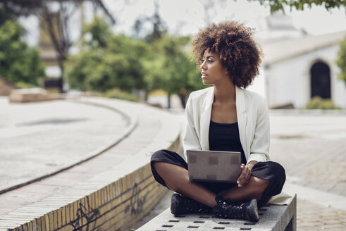 Fashionable young woman with curly hair sitting on bench with laptop - JSMF00216