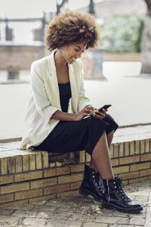 Smiling young woman with curly hair sitting on wall looking at cell phone - JSMF00219