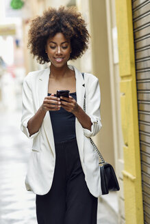 Portrait of smiling young woman with curly hair looking at cell phone - JSMF00225