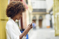 Young woman with curly brown hair looking at cell phone - JSMF00228