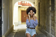 Portrait of smiling young woman listening music with headphones - JSMF00249