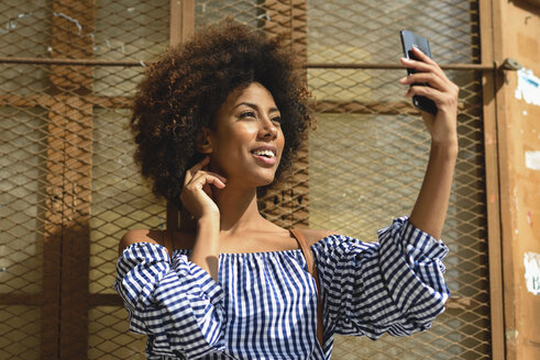 Smiling young woman taking selfie with cell phone - JSMF00255