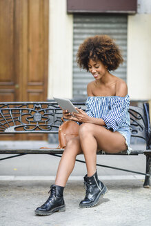 Young woman sitting on bench in the city using tablet - JSMF00258