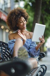 Smiling young woman sitting on bench with tablet having video chat - JSMF00264
