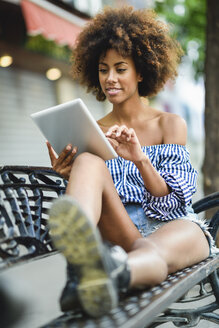 Portrait of young woman with curly hair sitting on bench using tablet - JSMF00267