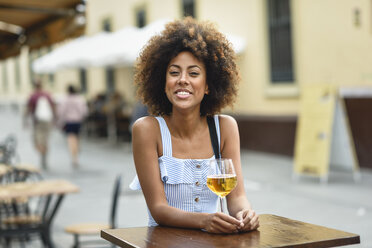 Portrait of happy young woman drinking beer outdoors - JSMF00270