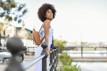 Portrait of fashionable young woman with camera and backpack - JSMF00273