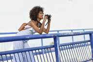 Smiling young woman standing on bridge taking pictures with camera - JSMF00276
