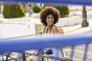 Portrait of smiling young woman with curly hair on a bridge - JSMF00279