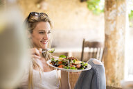 Young woman relaxing on garden patio eating salad - CUF21350