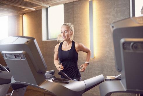Woman running on treadmill in gym - CUF21407