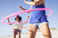 Women on beach using hula hoops - CUF21471